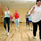 Aerobics class, senior woman in middle, smiling