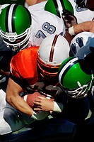 Football player being tackled by defenders(Digital Enhancement)