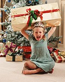 Girl (4-6) by christmas tree, holding present above head, portrait
