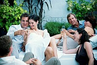 Six adults sitting outdoors, toasting with champagne, smiling
