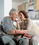 Mature couple on sofa, woman holding phone to man´s ear, smiling