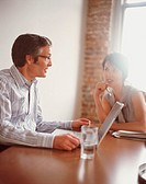 Businessman and businesswoman talking, man using laptop