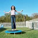 Girl (8-10) jumping on trampoline in backyard