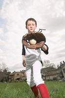 Boy (10-12) showing baseball in glove, portrait
