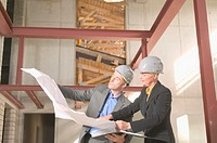 Man and woman wearing hard hats, looking at blue print in building
