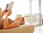 Young woman lying on sofa reading book (focus on woman´s face)