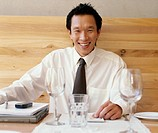 Businessman sitting in restaurant with laptop, smiling, portrait