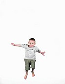 Boy (4-6) jumping, arms outstretched, smiling