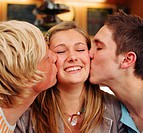 Teenage girl (15-17) being kissed by teenage boy and young man