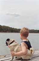 Boy (4-6) sitting on log beside lake, arm around pug, rear view