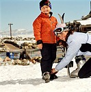 Mother adjusting son´s (4-6) ski boot, smiling, portrait