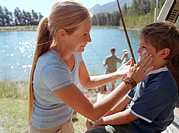 Woman rubbing sun cream on son´s (5-7) face, by lake, close-up