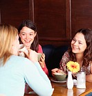 Three women in cafe with drinks, smiling