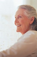 Senior woman smiling, side view