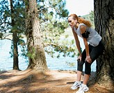 Young female jogger wearing earphones resting against tree by lake