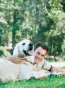 Young man lying on rug with dog in woodland, smiling
