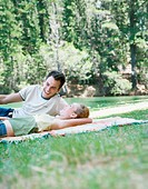 Young couple lying on rug in park, laughing