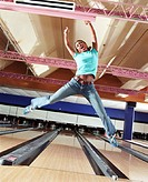 Young woman celebrating in bowling alley, portrait (blurred motion)