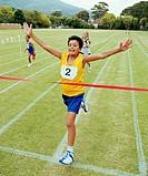Boy (10-12) crossing finishing line on running track, smiling