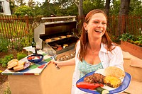 Woman grilling hamburgers and vegetables on barbecue grill, smiling