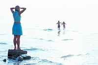 Italy, Lake Garda, mature woman on rock watching children play in surf