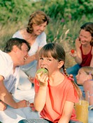 Family having picnic (focus on girl (6-8) eating apple)
