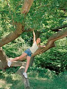 Girl (10-12) balancing on tree branch, looking up, smiling