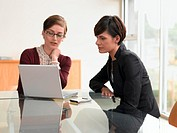 Two women sitting at conference table, looking at laptop