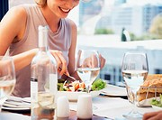 Young woman eating salad in restaurant, smiling, close-up