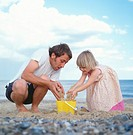Father and daughter (2-5) pouring sand into bucket on beach
