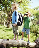 Two boys (6-8) on log, one wearing backpack, other holding binoculars