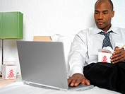 Businessman sitting on bed, using laptop and eating Asian food