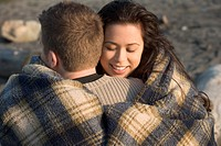 Young couple embracing on beach, wrapped in blanket, close-up