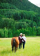 Young couple and horse walking across field of tall grass, rear view