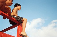 Man and boy (6-8) looking out from lifeguard hut, low angle view