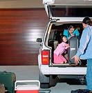 Family packing back of truck with suitcases