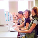 Group of high school students using computers in school library