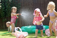 group of children playing outside with a hose pipe