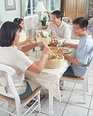 Parents with two children (11-13) eating meal at table