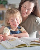 Mother and daughter (4-6) reading book, smiling