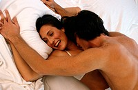 Romantic couple embracing on bed, elevated view