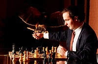 Business man holding falloon chess board