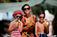 Mother with children having tropical drinks