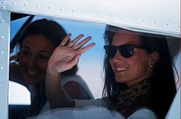 Women in aircraft waving hands, close up