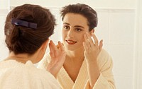 Woman applying cosmetics in mirror
