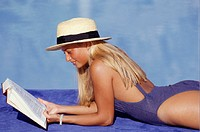 Woman reading book beside pool