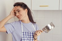 Young woman in kitchen holding saucepan