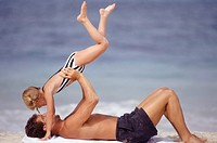 Father lying on beach lifting daughter (6-7)