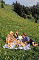 Family with daughter (8-9) having picnic on hillside
