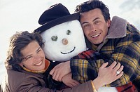 Couple embracing snowman, close-up